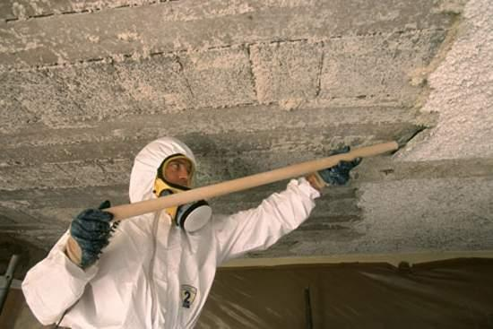 hazmat worker removing asbestos drywall from a ceiling